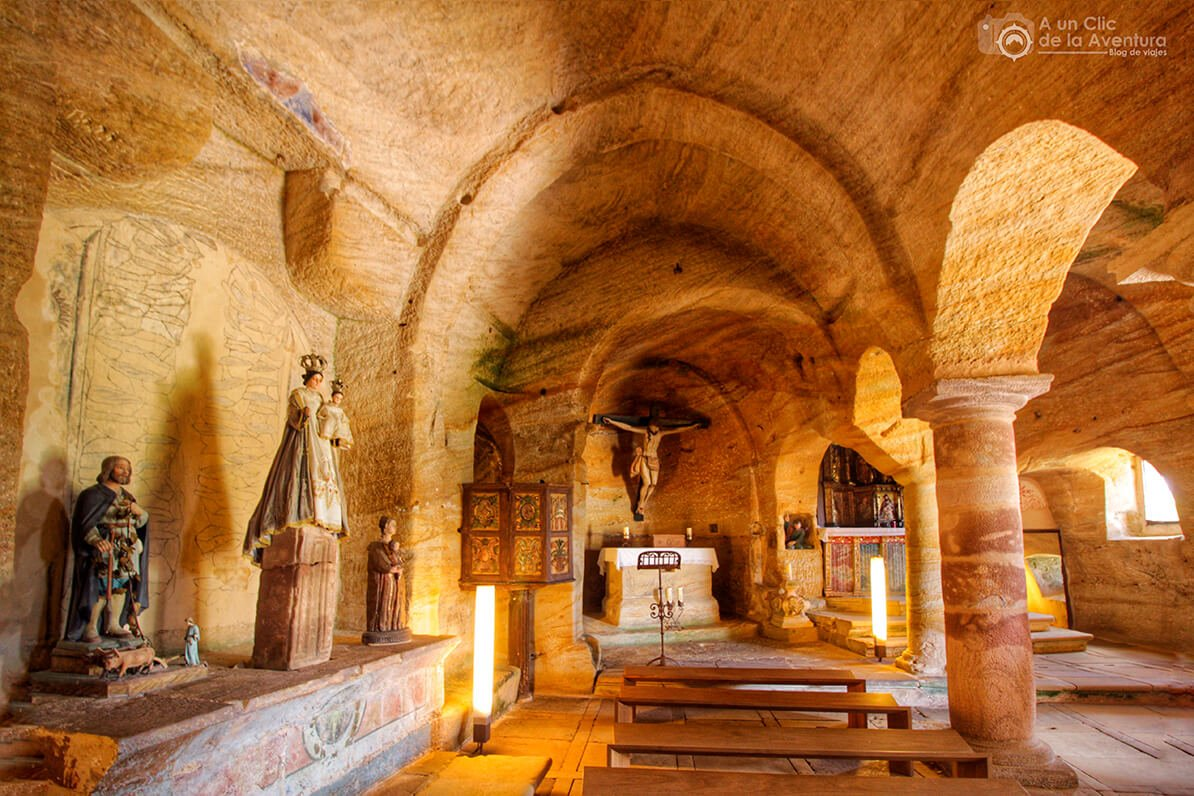 Nave izquierda de la iglesia rupestre de Olleros de Pisuerga con el púlpito, el ara romana y el Cristo crucificado del siglo XVII